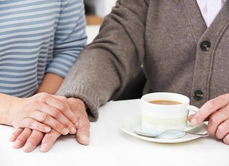 Daughter sharing tea with aging father