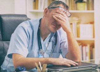 Doctor with computer rubbing forehead