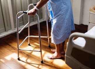 Elder person in hospital gown with walker 1500 x 1033
