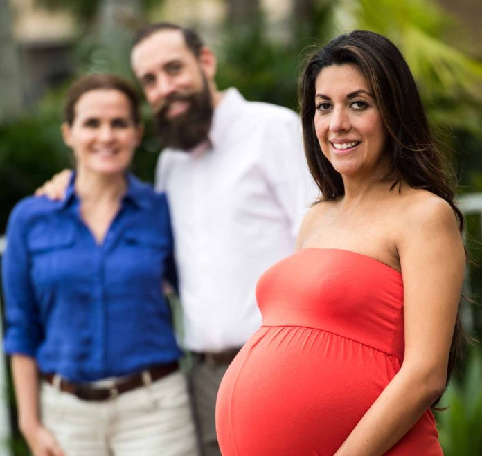 Pregnant Hispanic surrogate mother posing with the babies future parents 1414 x 1339