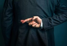 business man in suit with fingers crossed behind his back 1500 x 1001
