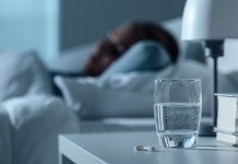 Woman sleeping in her bed at night, glass on water and pills on the foreground, medicine and treatment concept 1500 x 980