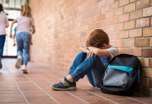 Young boy sitting on scholl corridor floor with hands over his face 1500 x 996