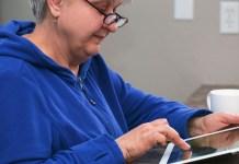 Senior-woman-in-blue-dress-working-on-tablet.jpeg