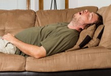 Man asleep on the couch with his mouth wide open snoring 1500 x 1000