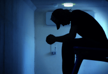 Depressed man in shadow with blue background 1144 x 674
