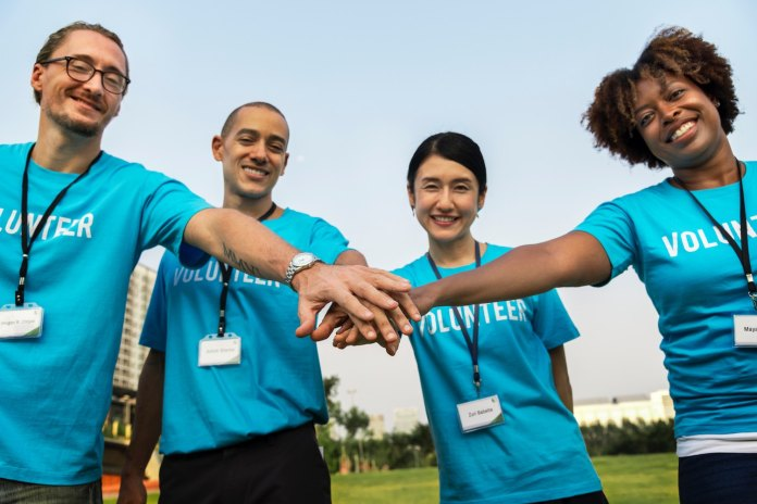 Young volunteers holding hands 1500 x 1000