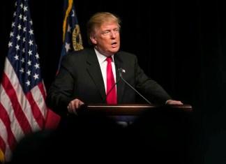 Trump speaking podium American flag