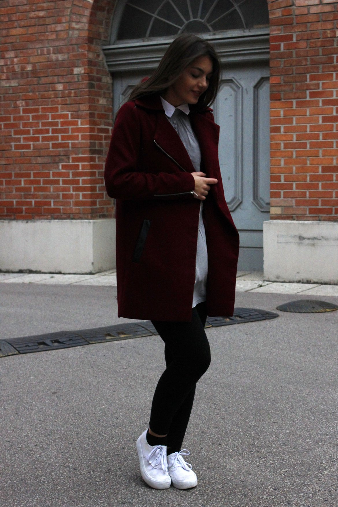 Dorie wearing a red coat and black legging and white shoes