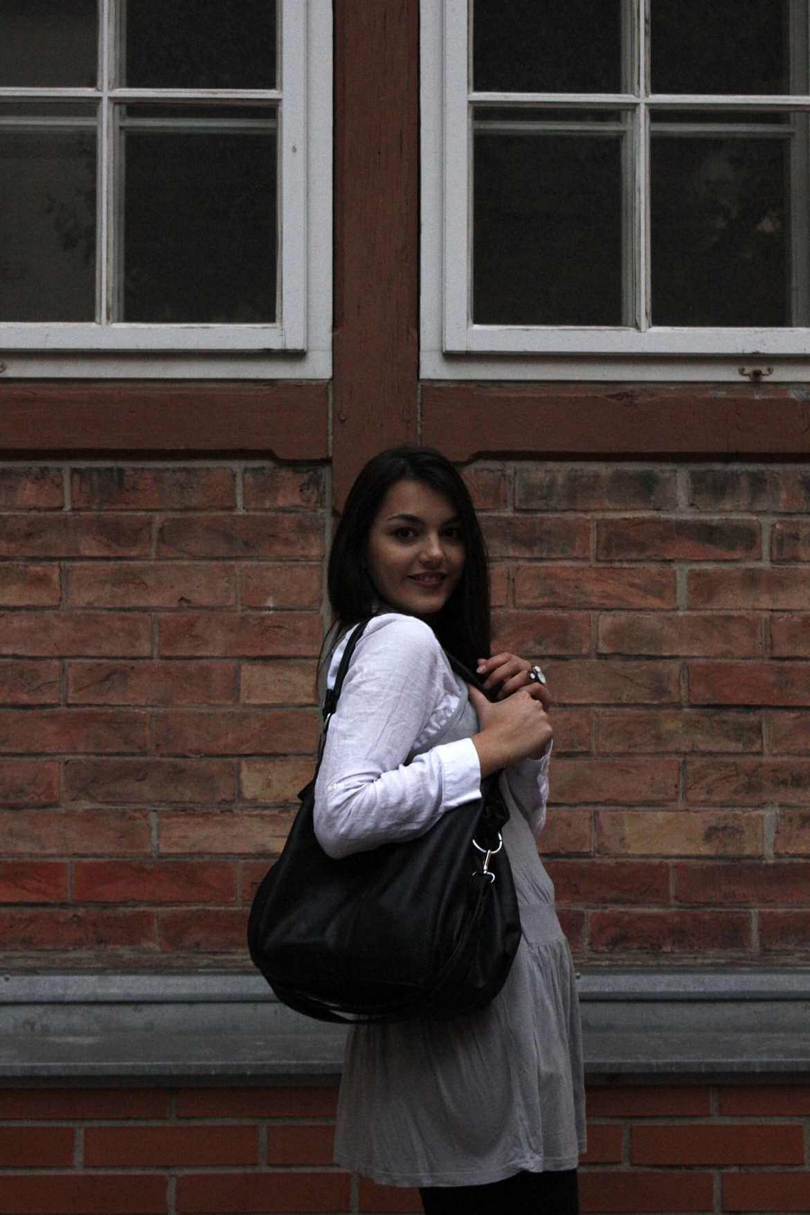 Dorie waring a black bag, grey dress and white blouse, looking to her side in to the camera