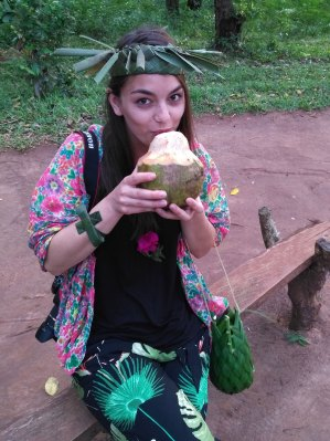 Dorie drinks fresh coconut and wears a hat made from palm leaves