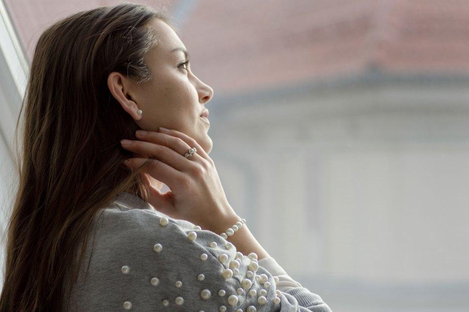 Dorie schaut aus dem Fenster, trägt einen Perlenpullover von Bershka und ein Armband von Christ