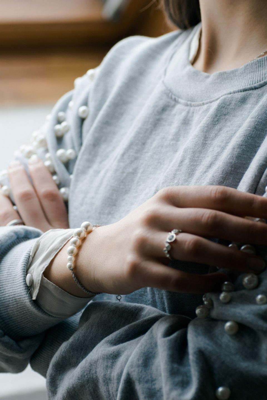Arme sind vor der Brust verschränkt, grauer Pullover von Bershka, Armband von Christ
