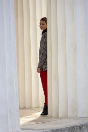 Dorie steht hinter einer Säule, trägt eine rote Hose vonl H&M, schwarze Heels von Mint&Berry und einen grauen Pullover