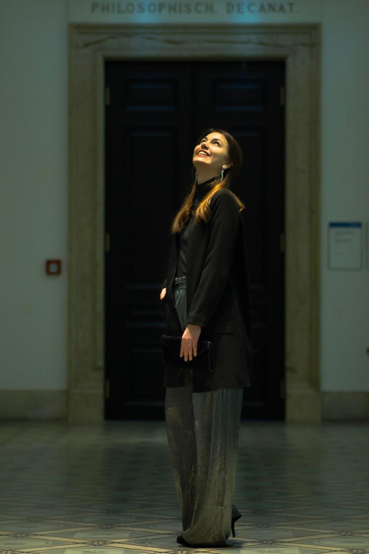 Dorie trägt ihr Silvester Outfit mit silberner Hose von Mango während sie in Lichtkegel lacht