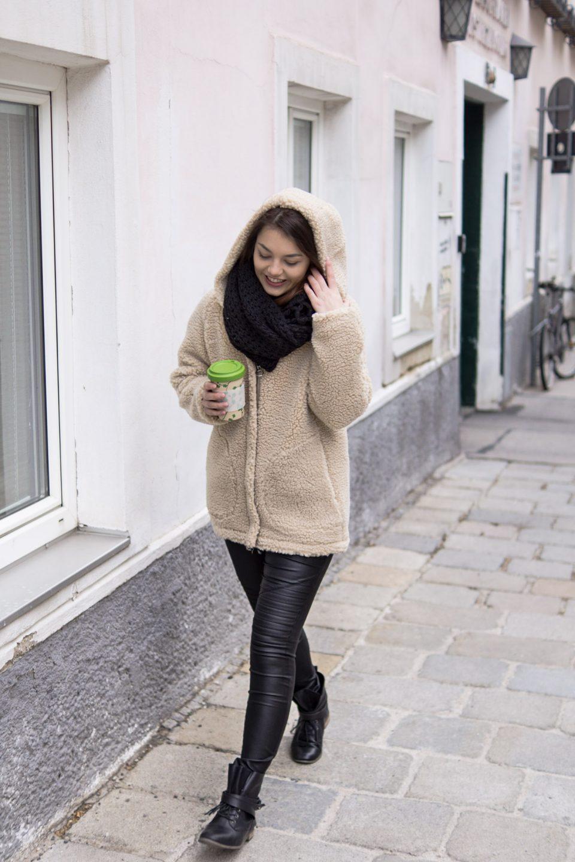 Dorie trägt eine Teddy Jacke und läuft die Straße mit einem Kaffeetogo Becher entlang