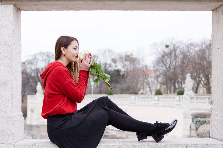 Dorie sitzt auf einer Mauer mit einem Strauß Rosen, roter Pulli von New Yorker, Rock Soyaconcept, Schuhe Mint & Berry