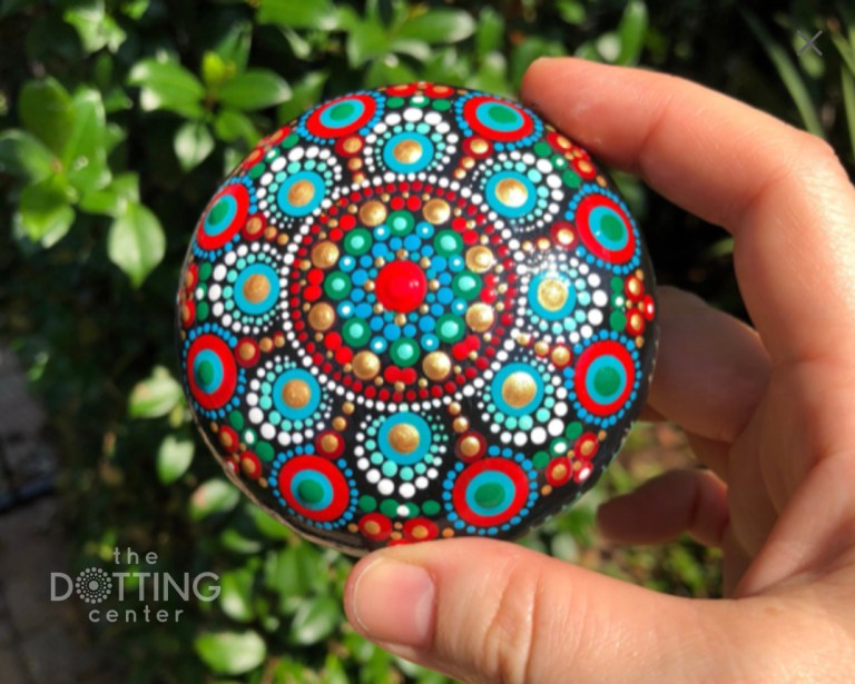 dot mandala on a wood pebble