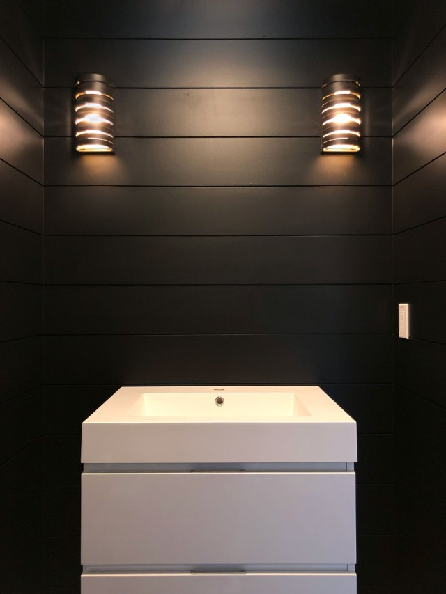 The addition of paint & lighting gives the powder room a beautifully dark & moody vibe.
