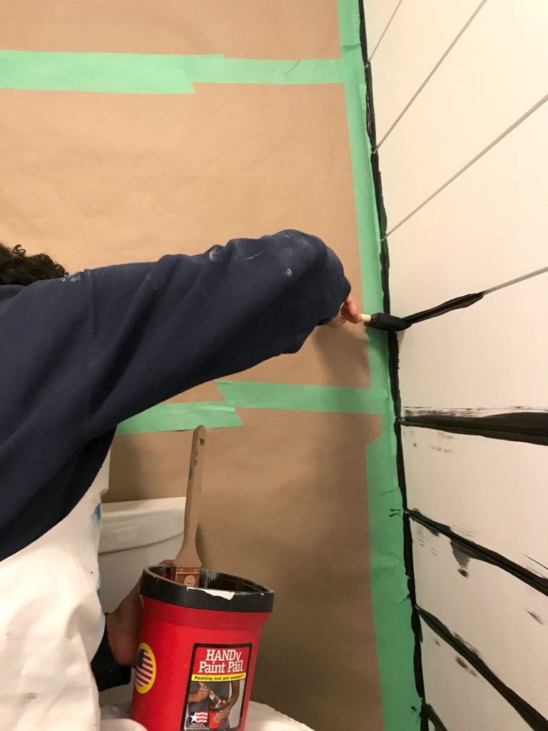 Getting started with painting our modern shiplap walls using a sponge brush to paint the gaps