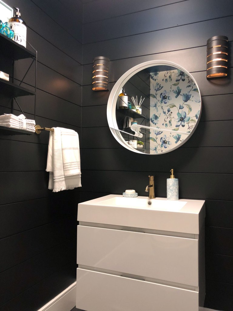 Our sleek and striking powder room reveal features black shiplap walls, a contrasting white vanity, bold patterned fabric wallpaper and gold accents
