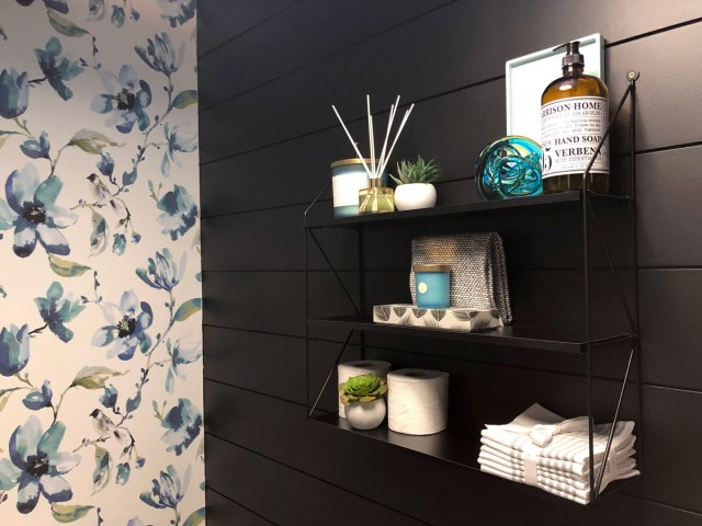 The black shelf from JYST house decor accents and provides functional storage to break up the black shiplap wall