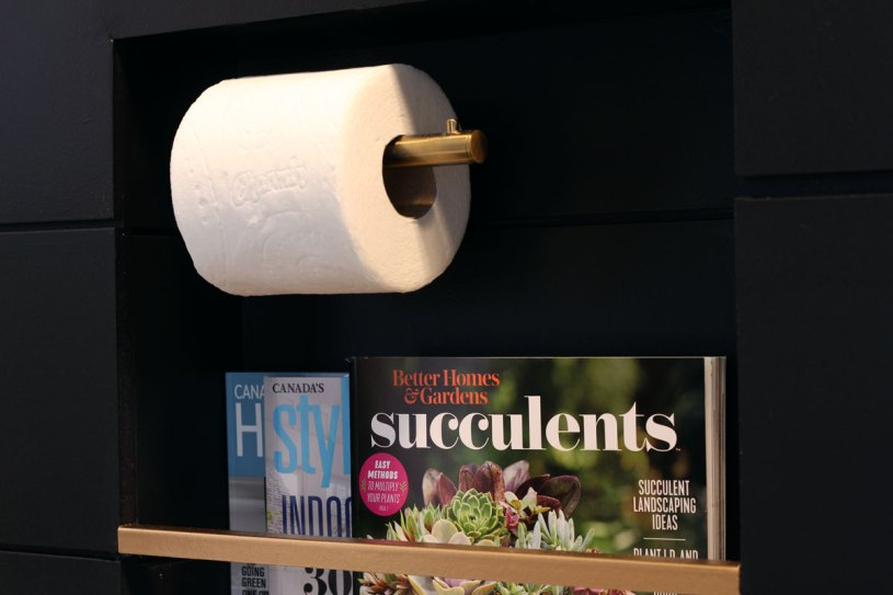 Magazines & toilet paper are inset into the wall in this stylish niche