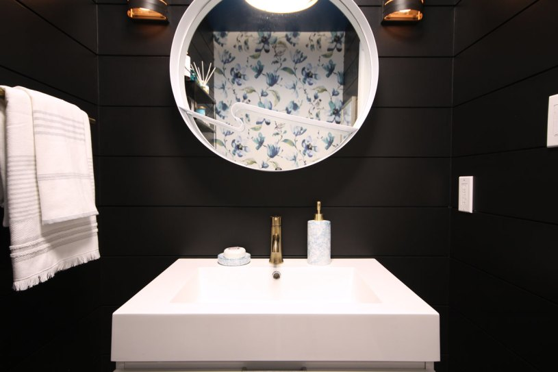 Love how the mirror reflects the contrasting patterned wallpaper bringing it into the forefront of the space