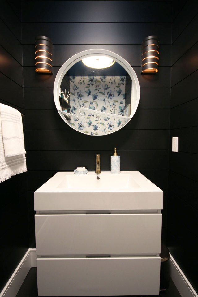 Black shiplap walls are a gorgeous contrast to the high gloss white vanity and white mirror.