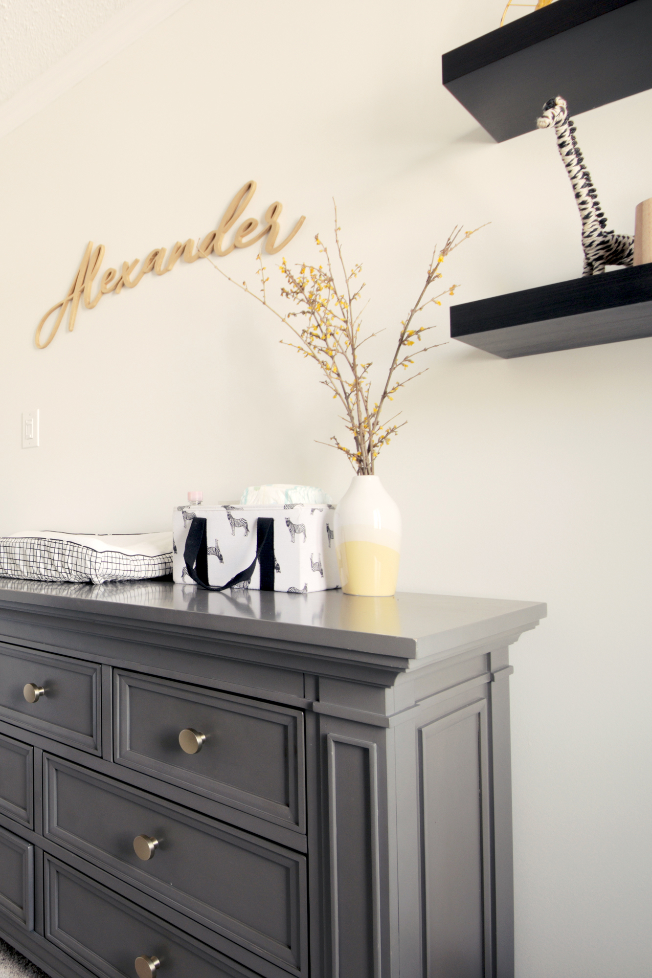 Champagne gold drawer knobs elevate the look of the dresser in this nursery reveal