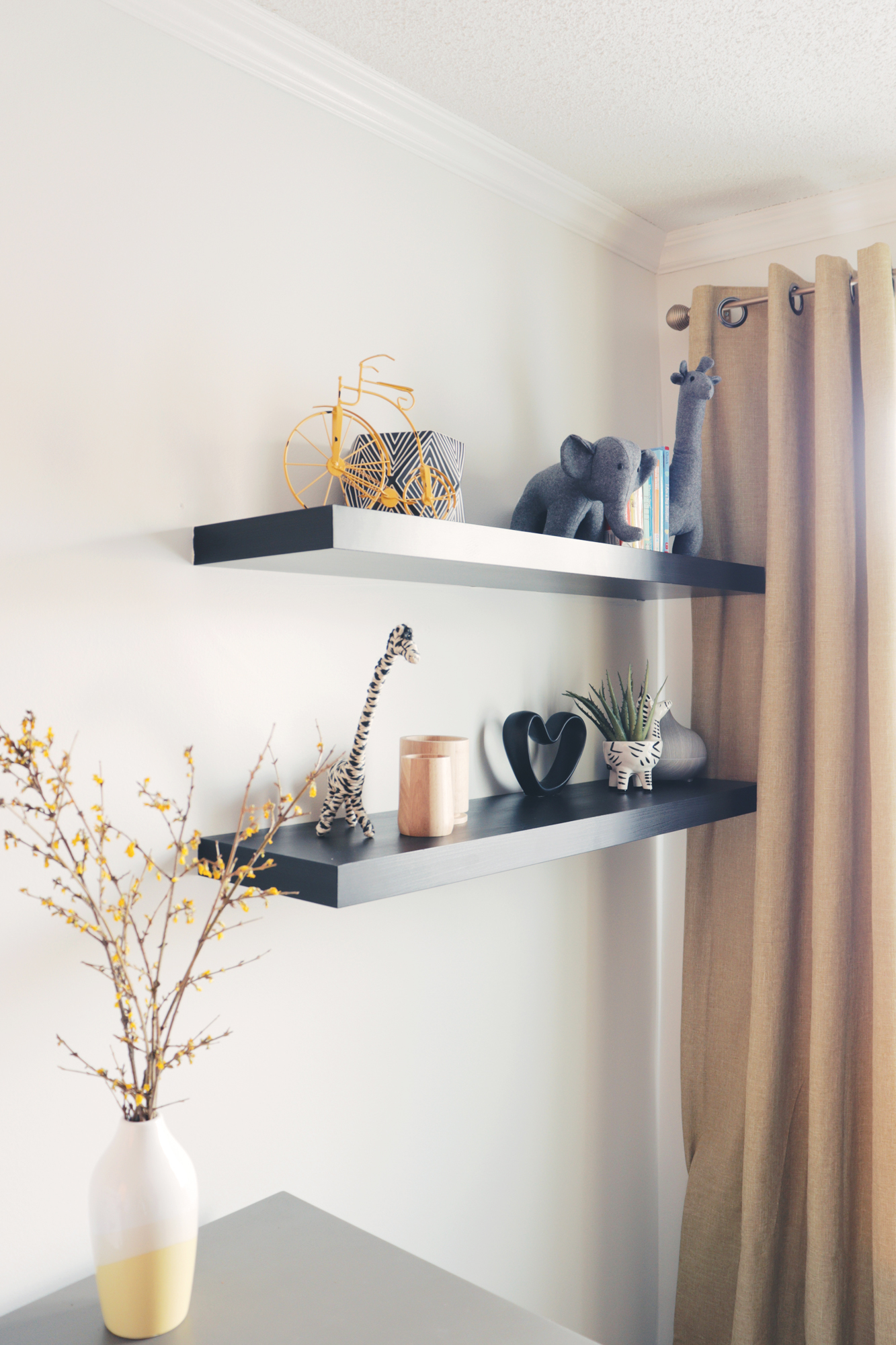 Floating shelves provide a place to store decorative and less used items freeing up the space on the change table