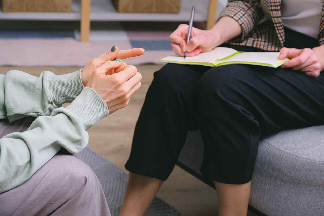 anonymous female therapist and client sitting in armchairs during session in modern office