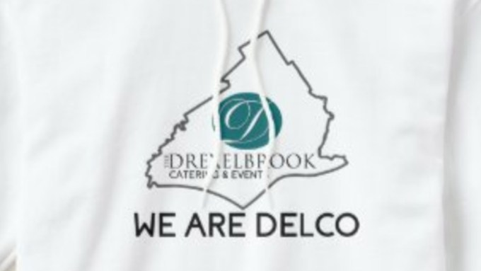 """Image of sweatshirt graphic. Bold letters read """"we are delco"""" while above it there is an outline of Delaware county with the drexelbrook ovel D logo and full """"The drexelbrook"""" logo inside. The sweatshirt is white."""