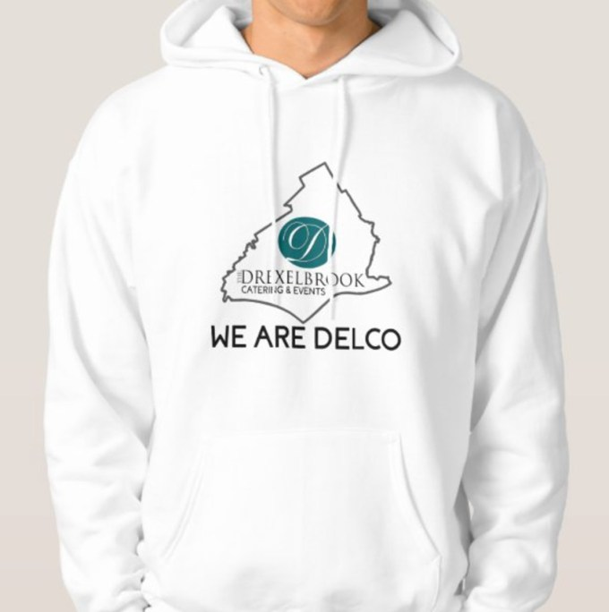 """Male model wearing white sweatshirt with the text """"WE ARE DELCO"""" and an outline of Delaware county, Pennsylvania with the Drexelbrook official logo inside."""