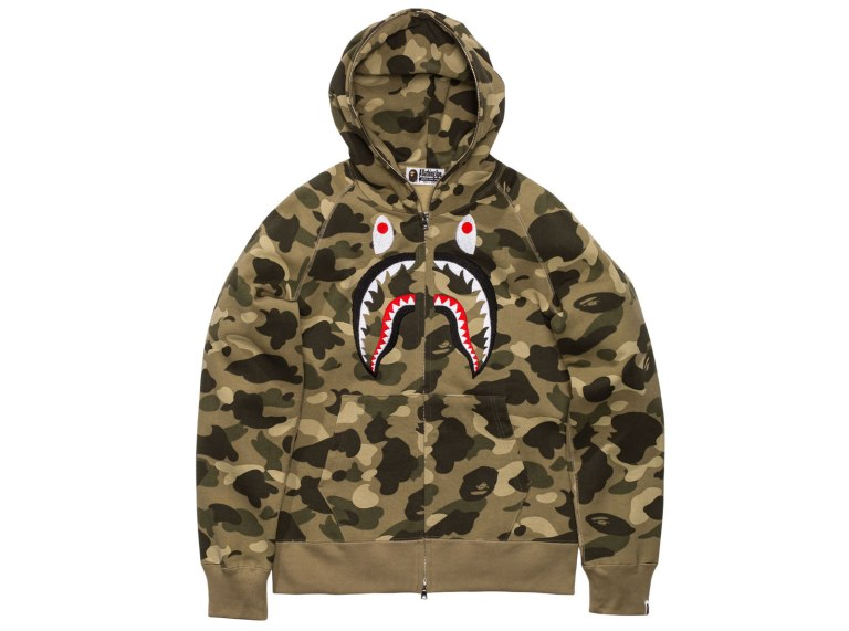At its high times there was nothing that was harder to get a hold of than the BAPE full zip shark hoodie. eBay was pretty much the only way to go and even there you did not come across that many, because people simply did not want to get rid of them. That is now a few years ago, but it almost feels like BAPE is already on a comeback, especially its most iconic pieces and it does not get much more iconic than this. For Summer 2016 A BATHING APE has now released the Color Camo Embroidery Shark Full Zip Hoodie. The hoodie comes in green, purple, red and blue camouflage versions, featuring the BAPE shark design embroidered across the front and varsity lettering embroidered on the back. Priced at $428, you can now get them from Undefeated and BAPE's own online store.