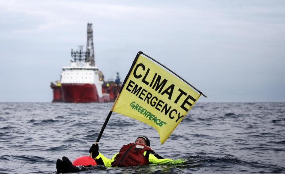 Greenpeace image of a protester in the sea with a 'climate emergency' flag
