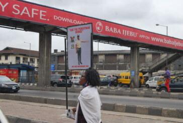 "Pedestrians shun overhead bridge despite inscription: '' Use the Pedestrian Bridge"" in Lagos."