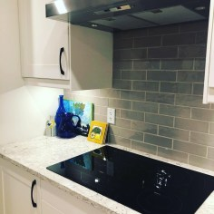The backsplash is a narrow subway tile in a soft grey and was taken all the way up the wall for a modern but classic look