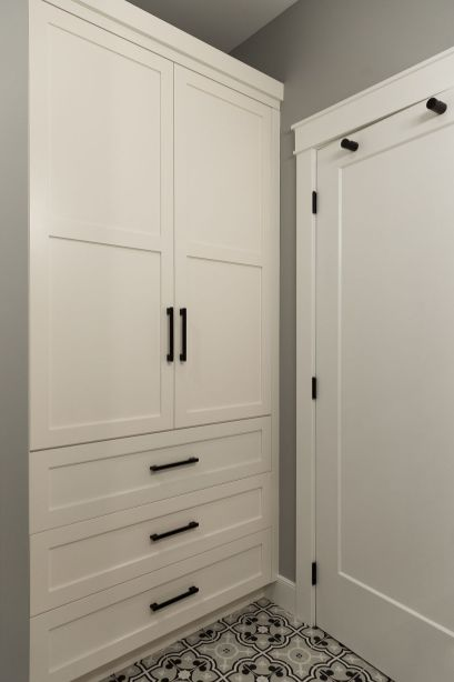 The main AND basement bathrooms both have these amazing built in storage cabinets nestled behind the doors- great use of space and they are beautiful too! Matte black hardware looks perfect with them!