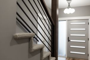 Cody made these incredible stair rails- he did the outside ones too! We had the crew stain the beam to match the exterior beams and added a cool but sophisticated light fixture from Matteo. The door is modern, but classic and has the perfect black hardware from Emtech