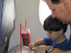 Father and son on a plane, Flying with KIDS - Tips for Flight Time, www.theeducationaltourist.com