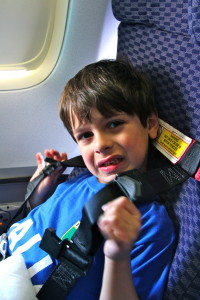 Boy wearing CARES restraint system on airplane, Flying with KIDS - Tips for Flight Time, www.theeducationaltourist.com