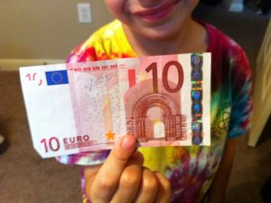 Boy holding 10 euro bill, Foreign Currency, www.theeducationaltourist.com