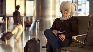 man in airport sleeping with ostrich pillow