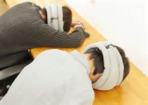 2 men with heads down on table sleeping with ostrich pillow