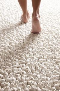 A 'carpet' of white porcelain skulls in the art piece What will you leave behind by Nino Sarabutra, Visiting Modern Art Museums with Kids, www.theeducationaltourist.com