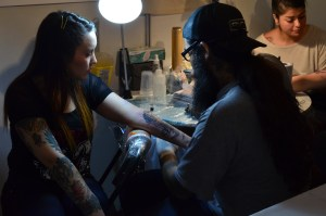 artist tattooing a woman's arm, US Creepy Places to Visit, www.theeducationaltourist.com
