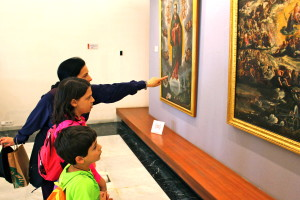 mother points to painting with children, travel myths
