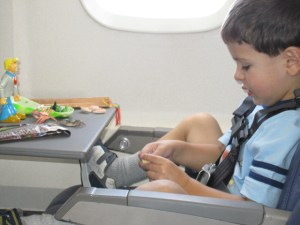 Boy playing with toys on airplane wearing kids fly safe belt, Safe Flying for Families, www.theeducationaltourist.com