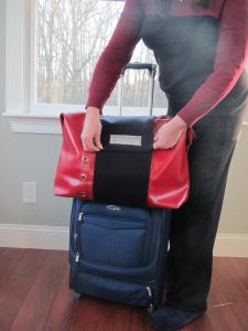 Demi Hugger holding red purse on luggage, Demi Hugger, www.theeducationaltourist.com